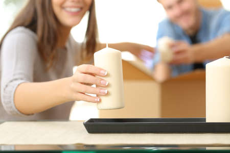 mate married: Close up of a happy couple hands unpacking a box when moving home and placing objects