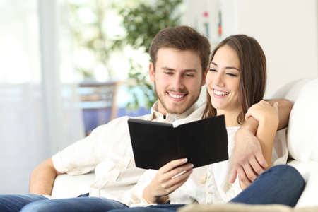happy couple: Couple together reading a guide in an ebook sitting on a couch at home