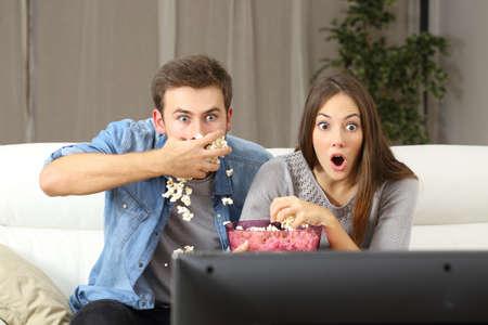 自宅のソファに座ってテレビ番組を見て驚かれるカップル