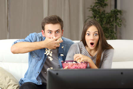 eating popcorn: Amazed couple watching tv program sitting on a couch at home