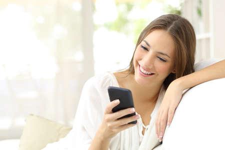 집에서 소파에 앉아 스마트 폰에서 메시지를 읽고 행복 한 소녀