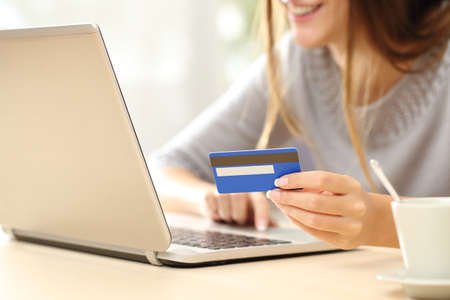 pagando: Primer plano de una mano de la mujer feliz de comprar en línea con un ordenador portátil y el pago con tarjeta de crédito