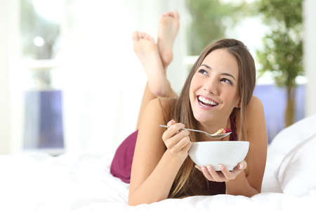 colazione: Ragazza in buona salute che mangia i cereali per la prima colazione sdraiato sul letto a casa o in albergo Archivio Fotografico