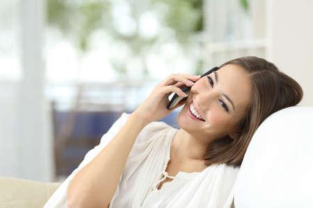 llamando: Niña feliz hablando por el teléfono móvil descansando en un sofá en casa Foto de archivo