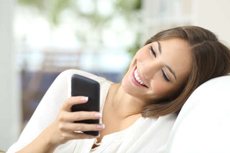 Happy girl texting on a mobile phone resting on a couch at home Stock fotó