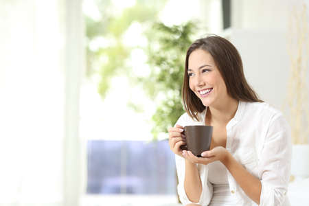 Pensive woman drinking coffee or tea and thinking looking sideways at home