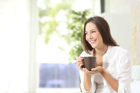 Zamyšlený žena, pití kávy nebo čaje a myšlení při pohledu z boku doma
