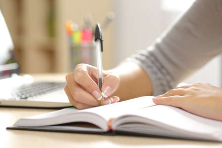 cerrar: Primer plano de una mujer escrito en una agenda en un escritorio en la oficina o en casa