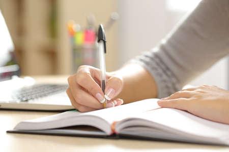 Zblízka žena rukou psaní v agendě na stole doma nebo v kanceláři
