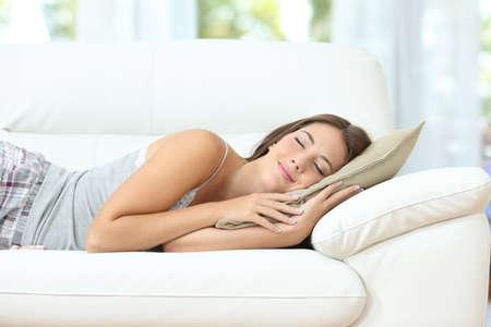 Krásná dívka spí nebo dřímání šťastný na pohodlném gauči doma