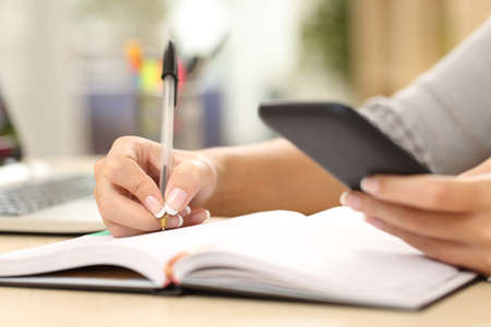 Woman hand writing in agenda consulting a mobile phone on a desk at home or office Foto de archivo