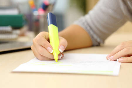 highlight: Close up of a student hand underlining a document on a desk at home