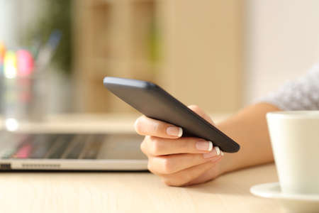Close up of a woman hand using a smart phone on a desk at home
