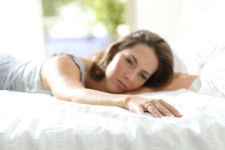 pareja en la cama: Novia triste falta su novio tocar con la mano el lado vacío de la cama