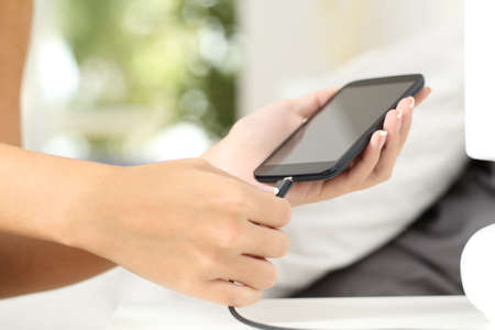 unplugging: Woman hands plugging a charger in a smart phone in the bedroom at home