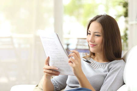 self exam: Student studying and learning reading notes siting on a couch in the living room at home