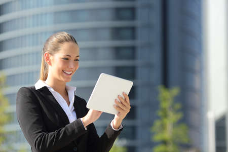 career young: Happy business woman using a tablet in the street with office buildings in the background