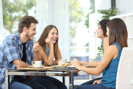 Group of 4 happy friends meeting and talking and eating desserts on a table at home