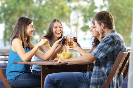 Grupo de 4 amigos felices que tuestan en una terraza del hotel o en el hogar Foto de archivo