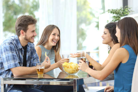 Funny group of 4 friends having a conversation and drinking at home Stock Photo