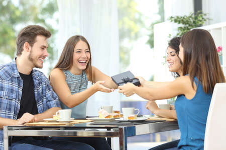 Friends celebrating birthday and giving gift to a girl sitting in a dining room Standard-Bild