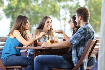 juventud: Grupo de cuatro amigos hablando y bebiendo sentado en una terraza en el hogar