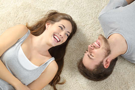 Happy couple laughing looking each other and lying on a carpet at home