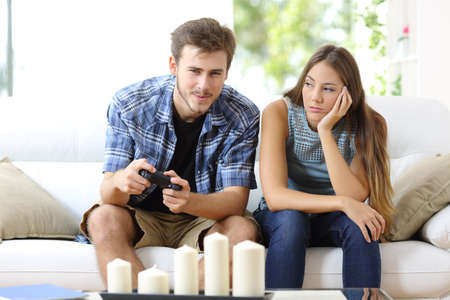 angry: Man playing video games at home and his girlfriend bored beside looking at him Stock Photo