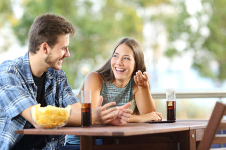 students talking: Girl talking with a friend in a terrace with snacks and drinks Stock Photo