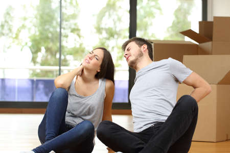 Tired couple moving home suffering backache sitting on the floor