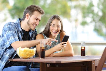 Paar teilen ein Smartphone auf einem Hotel oder zu Hause Terrasse sitzen Standard-Bild