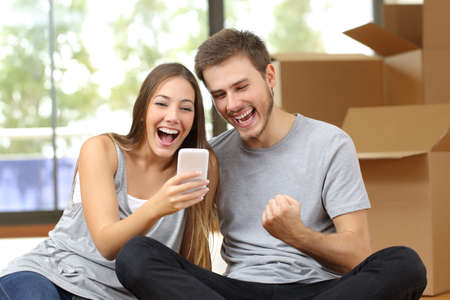 Euphoric couple sitting on the floor moving house and watching smart phone Imagens