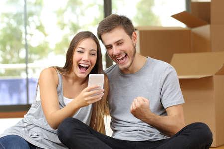 triunfador: Pareja de euforia que se sienta en el suelo de una mudanza y viendo teléfono inteligente