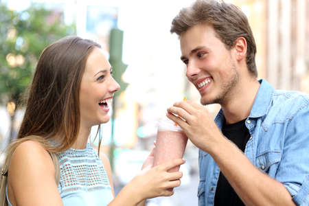 sharing: Couple or friends sharing a milkshake and laughing in the street Stock Photo