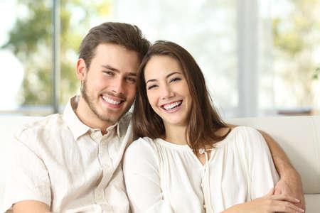 Šťastný pár sedí na gauči doma a díval se na kameru