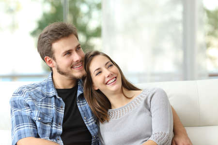 attractive couch: Happy couple thinking and looking sideways sitting on a couch at home