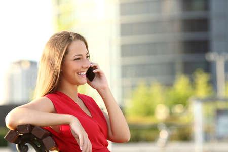 preguntando: mujer empresaria hablando por teléfono móvil que se sienta en un banco en la calle con edificios de oficinas en el fondo