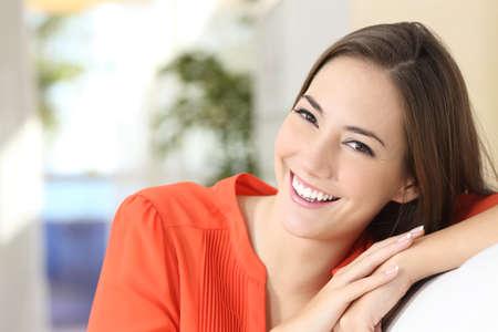 Schoonheid vrouw met perfecte witte tanden en glimlach draagt een oranje blouse kijken naar de camera, zittend op een bank thuis Stockfoto