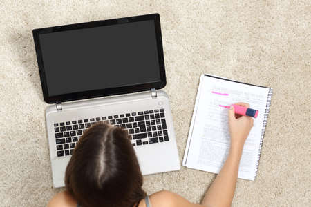 highlighting: Girl studying with a laptop and highlighting in a notebook lying on the floor at home
