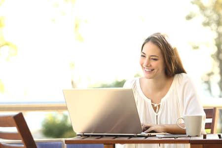 Ondernemer vrouw werken met een laptop in een coffeeshop of thuis terras Stockfoto