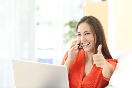 happy customer: Happy confident entrepreneur working with a laptop gesturing thumbs up looking at camera sitting on a couch at home Stock Photo