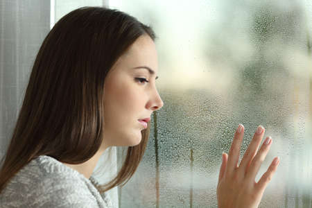 Sad woman looking the rain falling through a window at home or hotel Stock Photo