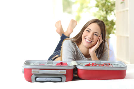 Happy woman planning a travel preparing a suitcase and looking at camera