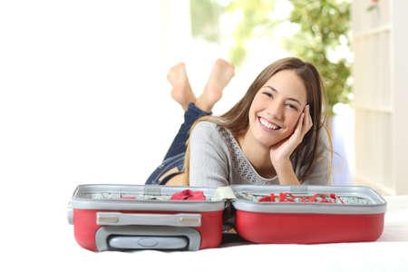 Gelukkige vrouw het plannen van een reis voorbereiden van een koffer en kijken naar de camera