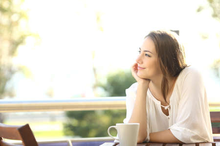 meditating: Pensive happy woman remembering looking at side sitting in a bar or home terrace
