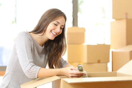 belongings: Woman packing or unpacking belongings in a carton box when moving home