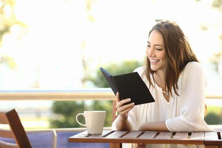 Kobieta zrelaksowany czyta książkę w czytnik ebook w barze lub w domu