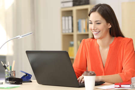 Hermosa profesional independiente que trabaja con un ordenador portátil en un escritorio en la sala de su casa u oficina