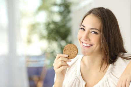 biscuits: Happy girl showing a dietetic cookie sitting on a couch at home Stock Photo