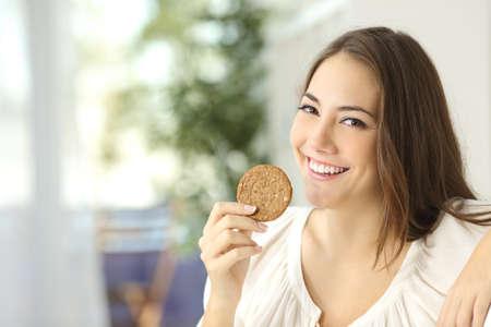 Ragazza felice che mostra un biscotto dietetico seduto su un divano a casa Archivio Fotografico